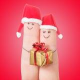 Visages de doigts dans des chapeaux de Santa avec le boîte-cadeau Couples heureux Photo libre de droits
