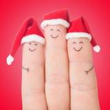 Visages de doigts dans des chapeaux de Santa Célébration heureuse de famille Photos libres de droits
