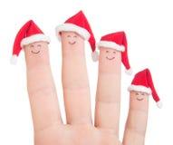 Visages de doigts dans des chapeaux de Santa Famille heureuse célébrant le concept Images libres de droits