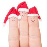 Visages de doigts dans des chapeaux de Santa Famille heureuse célébrant le concept Photo stock