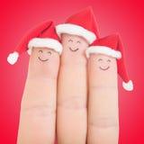 Visages de doigts dans des chapeaux de Santa Famille heureuse célébrant le concept Photos stock