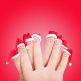 Visages de doigts dans des chapeaux de Santa Famille heureuse célébrant le concept Image libre de droits