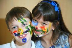 Visages de peintures d'enfants avec des couleurs photos stock