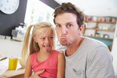Visages drôles d'And Daughter Making de père au Tableau de petit déjeuner images stock