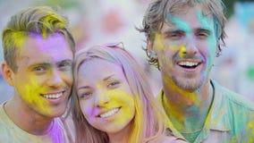 Visages enthousiastes des beaux jeunes couverts en couleurs souriant à l'appareil-photo banque de vidéos