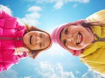 Visages heureux de petites filles au-dessus de ciel bleu Photos stock