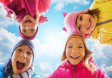 Visages heureux de petits enfants au-dessus de ciel bleu Image stock
