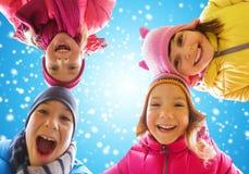 Visages heureux de petits enfants au-dessus de ciel bleu et de neige Image stock