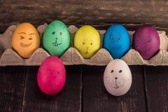 Visages mignons colorés d'oeufs de pâques sur le fond en bois Deco drôle Images libres de droits