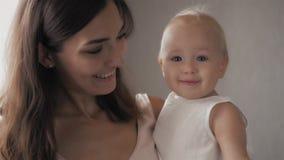 Visages riants de famille heureuse, mère tenant le bébé garçon adorable d'enfant, souriant et étreignant, fin vers le haut de la  Images stock