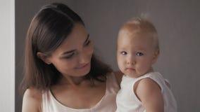 Visages riants de famille heureuse, mère tenant le bébé garçon adorable d'enfant, souriant et étreignant, fin vers le haut de la  Photo stock