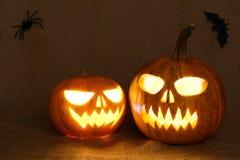 Visages rougeoyants effrayants de potirons Potirons effrayants de Halloween sur un fond de toile de jute Photo stock