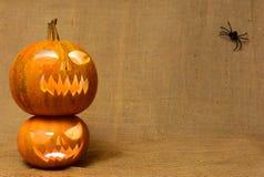 Visages rougeoyants effrayants de potirons Potirons effrayants de Halloween sur un fond de toile de jute Photos libres de droits