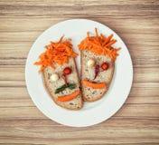 Visages végétaux faits en pain, fromage, piments, tomates et carr Images stock