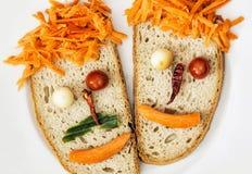 Visages végétaux faits en pain, fromage, piments, tomates et carr Photographie stock