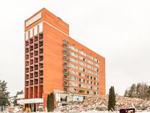 Visaginas Litauen - 12 Februari 2018: Dagvintersikten sköt av rivning av det Aukstaitija hotellet Royaltyfria Bilder