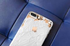 VISAGINAS LITAUEN - MARS 30, 2019: Den tillbaka sidan av en bruten iPhone 8 plus är vit, och guld- på en blått piska bakgrund fotografering för bildbyråer