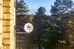 Visaginas Litauen am 1. Oktober 2018: Dreifarbiger Satellitenluftantennenteller auf Backsteinmauer über Kiefernholz lizenzfreie stockfotografie