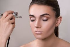 Visagist που κάνει makeup για το πρότυπο με το αερογράφο, που απομονώνεται στο γκρι Υπόβαθρο με το αερογράφο εκμετάλλευσης χεριών στοκ εικόνα με δικαίωμα ελεύθερης χρήσης