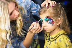 Visagist крася сторону маленькой девочки стоковые изображения