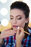Visagist applying lipstick to woman Stock Image