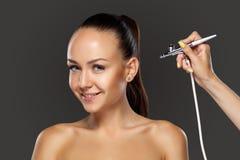 Visagist, das Make-up für Modell mit Aerografie macht Stockfotografie