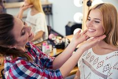 Visagist looking at woman`s makeup in salon Stock Photo