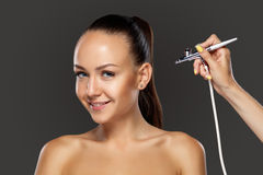 Visagist making makeup for model with aerograph Stock Photography