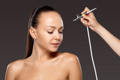Visagist making makeup for model with aerograph Royalty Free Stock Photo