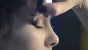 Visagist op de ooglidvrouw doet beige schaduw met een borstel stock footage