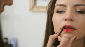 Visagist paints with red lipstick a woman`s lips stock video