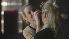 Visagist profesional que aplica los cosméticos del maquillaje en cara de la mujer en salón de belleza almacen de video
