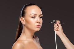 Visagist que hace el maquillaje para el modelo con el aerógrafo Imágenes de archivo libres de regalías