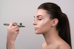 Visagist som gör makeup för modell med aerographen som isoleras på grå färger Bakgrund med handinnehavaerographen Visagist genom  royaltyfri foto