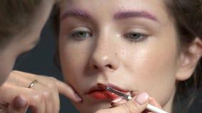 Visagist usando cepillo del lápiz labial almacen de metraje de vídeo