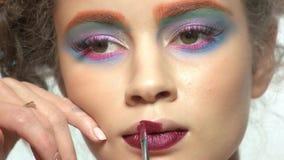Visagist is using lipstick brush. Female model, colorful artistic makeup stock video