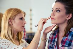Visagist woman applying makeup Stock Images