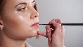 Visagiste应用在俏丽的妇女的嘴唇的自然色的润发油 股票录像