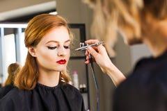 Visagiste που κάνει το κορίτσι το επαγγελματικό makeup που χρησιμοποιεί ένα airbrush Στοκ Φωτογραφία