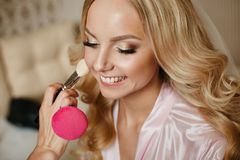 Visagiste applies makeup for a beautiful blonde girl with wedding hairstyle and shiny smile stock photography
