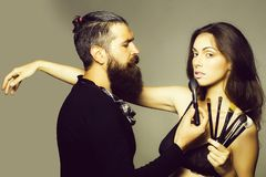 Visagiste bearded man and woman. Young couple of women with pretty face and long brunette hair in black bra on body and handsome bearded men visagiste with royalty free stock images