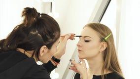 Visagiste de la mujer que hace las cejas y la cara del maquillaje encendido para la mujer joven antes de casarse Cejas del colora metrajes