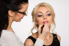 Visagiste doing make-up of a beautiful young girl Royalty Free Stock Photo