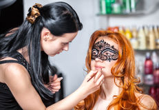 Visagiste a doing make-up to the young girl Stock Image