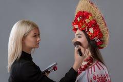 Visagiste faisant le maquillage au modèle photos stock