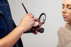Visagiste kvinna på arbete i en skönhetstudio som gör makeup till en flicka i hennes händer som rymmer en palett med pulver och b royaltyfri fotografi