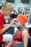 Visagiste maakt make-up voor modelslijtage Arabische tulband Stock Foto's