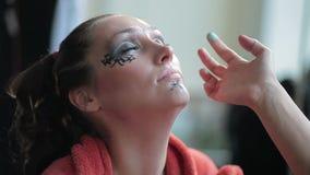 Visagiste makes makeup for  model, professional makeup artist tints the model's eye,makeup, body art stock footage