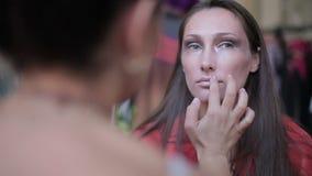 Visagiste makes makeup for  model, professional makeup artist tints the model's lips,makeup, professional makeup stock video