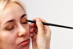 Visagiste med en borste i en hand som sätter makeup på ögonen av modellen, den annan handen, drar huden av ögonlocket med guld fotografering för bildbyråer